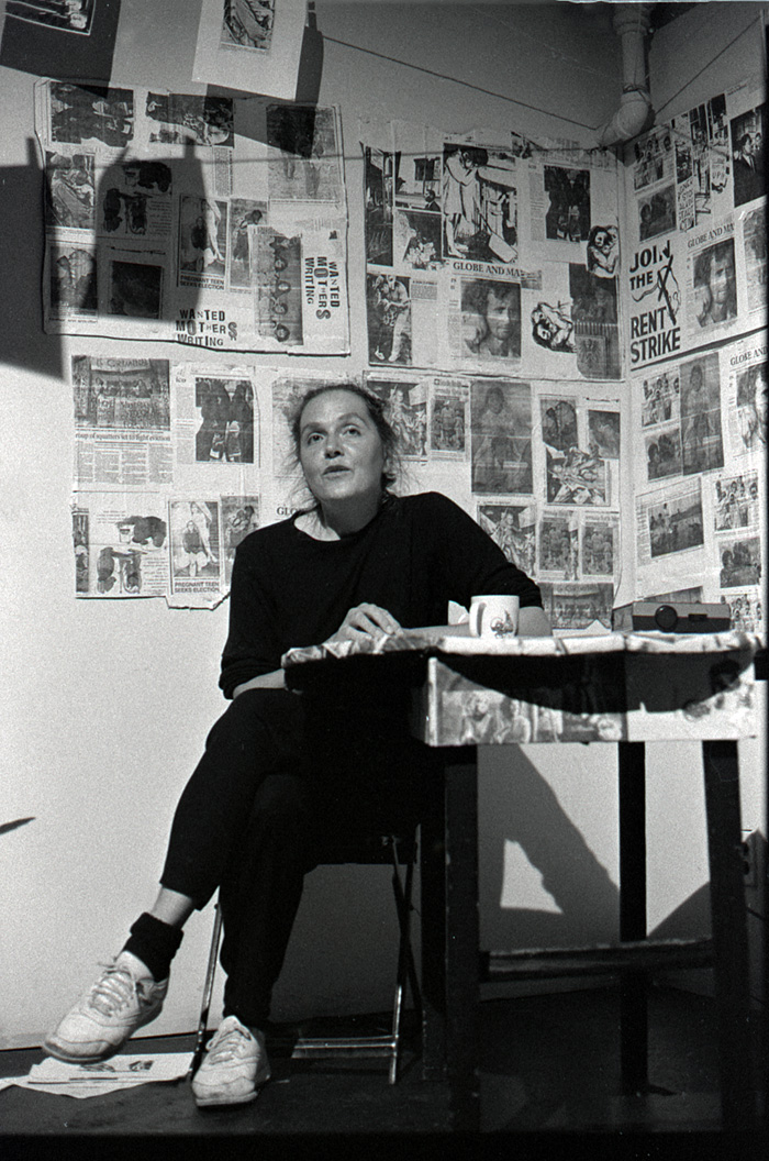 1991_09_12_Performance_Performance_Poets_Series_My_Secret_Kitchen_Margaret_Dragu_Dragu_seated_at_kitchen_table_articles_pasted_behind