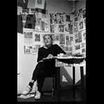 Margaret Dragu seated at kitchen table newspaper articles on wall behind her