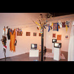 """The Stone Show"" - Zachery Longboy installation three TV monitors on plinths clothes hanging prints on wall"