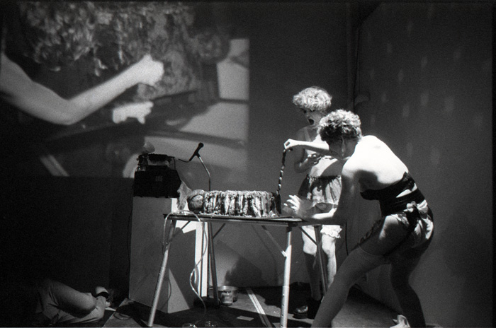 1990_09_12_Performance_Eating_with_Emily_at_grunt_gallery_Faryna_centre_with_back_to_camera_Jonathan_Wells_behind