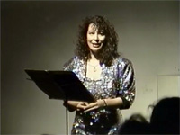 Michael Vonn in an evening gown speaking behind a music stand